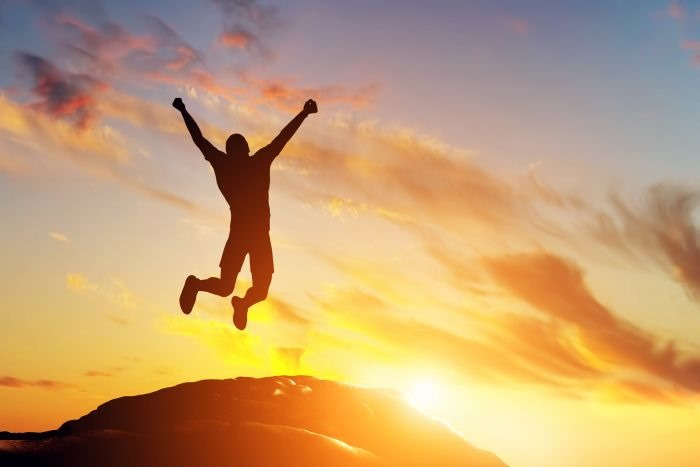 happy-man-jumping-for-joy-on-the-peak-of-the-mountain-at-sunset-success-42811168